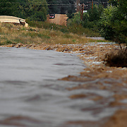 WIGGINS, CO - SEPTEMBER 14: A deer is trapped on a temporary island by rising flood waters from the South Platte River as heavy rains for the better part of week fueled widespread flooding in numerous Colorado towns on September 14, 2013. (Photo by Marc Piscotty/ © 2013)