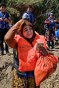 Refugee lady, still shocked by the fear she experienced during her dangerous trip, praying to a small Koran that she caries with her. <br /> Refugees arriving on beaches near Molyvos village in Lesvos island. Thousands of them come from Turkey, crossing the sea border on inflatable dinghy boats, on a dangerous trip that has claimed many lives. Local people or NGOs expect them and help them in some places but after their arrival, most of them have to walk to the nearest village where they can hope for a places on busses that can take them to the city of Mytilene where they can register and eventually board on a ferry to Athens. Many decide to walk the distance as the busses aren&rsquo;t enough to accommodate the large number of people that arrive daily.