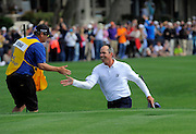Matt Kuchar celebrates a birdie out of the bunker on the 18th green to win with his caddie during the final round of the RBC Heritage golf tournament in Hilton Head Island, S.C., Sunday, April 20, 2014. Kuchar won the tournament with 11-under par. (AP Photo/Stephen B. Morton)