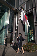 Office employees in Marunouchi area, passing by the Japanese flag.