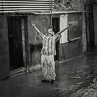 Man standing and welcoming the rain  as the Streets of San Miguel de Allende are flowing with water after the first rain in months when the rain season started.