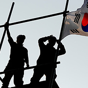 Korean nationalists hang a Korean flag at the Japanese embassy in Seoul, South Korea, during a protest against Japan's claim to Dokdo, a disputed islet in the East Sea. South Korea administers the territory and has a police presence there, but Japan, which calls the island Takeshima, has attempted recently to stake its own claim to Dokdo.