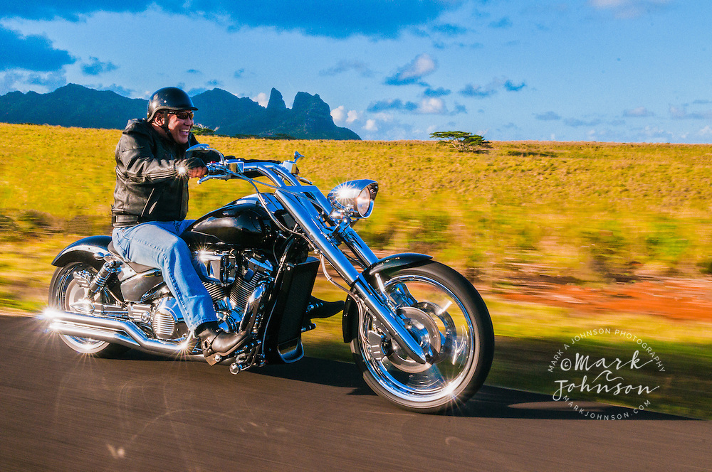 Hawaiian man riding road motorcycle, Kauai, Hawaii