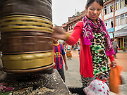 31 JULY 2015 - KATHMANDU, NEPAL:   A woman spins a prayer wheel while processing around Bodhnath Stupa. Bodhnath Stupa in the Bouda section of Kathmandu is one of the most revered and oldest Buddhist stupas in Nepal. The area has emerged as the center of the Tibetan refugee community in Kathmandu. On full moon nights thousands of Nepali and Tibetan Buddhists come to the stupa and participate in processions around the stupa. The stupa was heavily damaged in the earthquake of 25 April 2015 and people are no longer allowed to climb on the stupa, now they walk around the base and pray with butter lamps. PHOTO BY JACK KURTZ