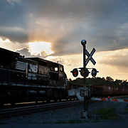 Dramatic clouds at sunset over a gated railroad crossing with a freight train passing in Waverly,  Virginia May 6, 2010