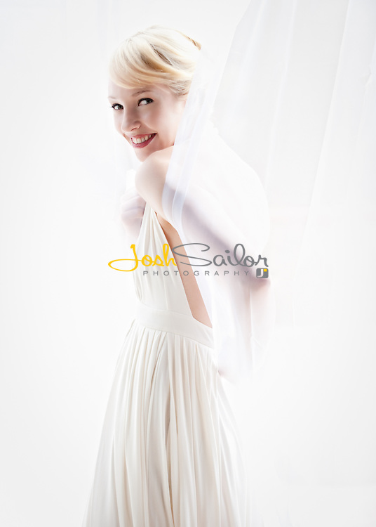 Blonde woman in white gown in front of white curtains