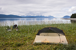 A kayaker checks their kayak at their wilderness campsite on Young Island in Glacier Bay National Park and Preserve located in the Beardslee Islands of the park in southeast Alaska. In the background is the Sitakaday Narrows of the main bay of the park.