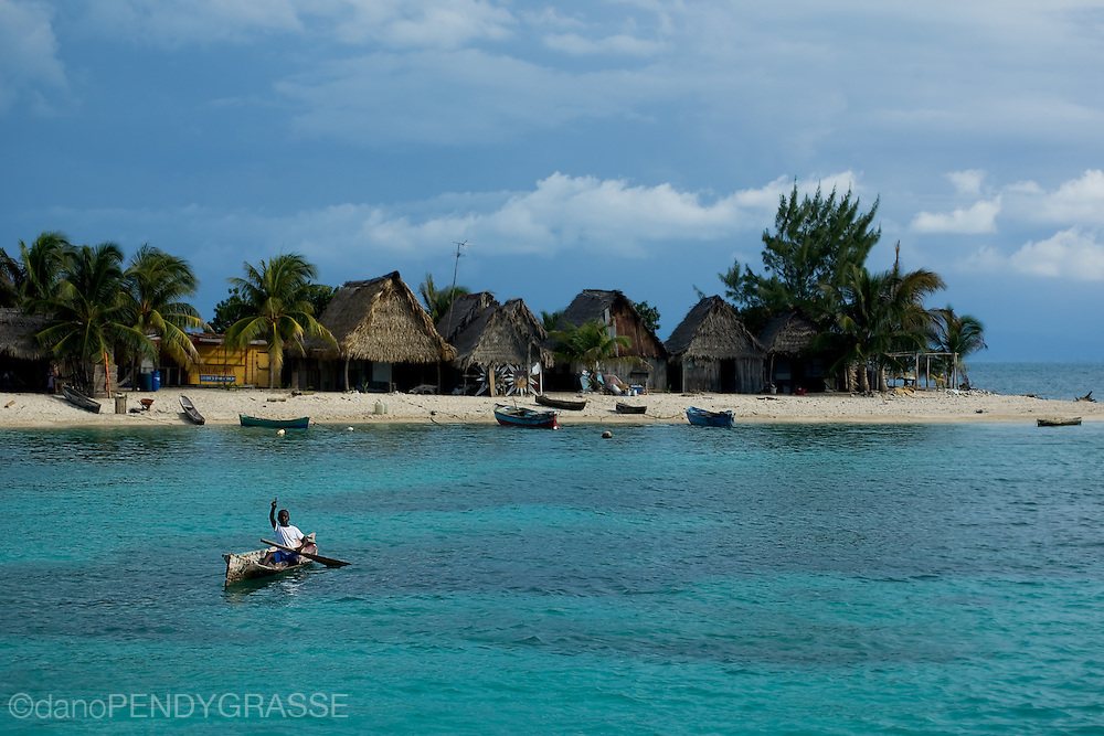 A boy in a dugout canoe paddles out from his fishing village in Cayos Cauchinos, Bay Islands, Honduras.