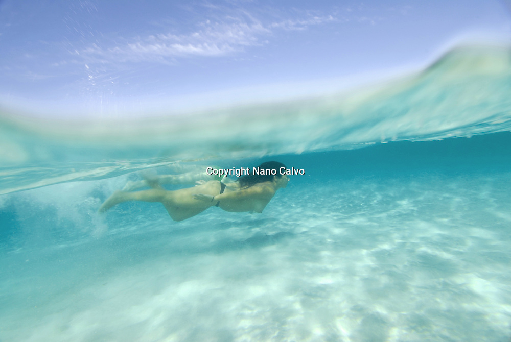 MR Young girls swimming and diving in the clear waters of Formentera, Balearic Islands, Spain © Nano Calvo