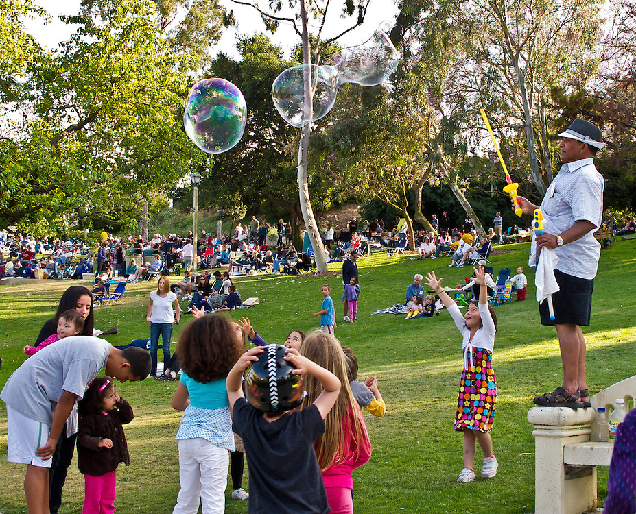 Afternoon in the park. The girl on the right, with her hands up, caught my attention. She seemed fascinated by the magic of the floating bubbles above her. And why is the bubble maker so serious? And why does the little girl on the left seem to cry?