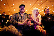 "Bunny Ranch brothel owner Dennis Hof, left, and sex worker Cami Parker, right, cheer for GOP presidential candidate Rep. Ron Paul at the Grand Sierra Resort in Reno, Nev., February 2, 2012. Hof and Parker were at the event, ""Pimping for Paul."""