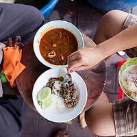 Worker's have a breakfast of larb and tom yum soup with rice in their shop in Chiang Mai, Thailand