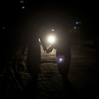 Two women walking hand in hand on a dark street in the north of Gaza City. Due donne si tengono per la mano mentre camminano al buio in una strada al nord di Gaza City.