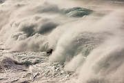 Huge Atlantic waves roll in from the West and rear up over the reef at Cape Cornwall near St Just, Penwith, South West Cornwall. These waves were approximatey twenty feet tall and absolutely packed with ocean energy. White horses can clearly be seen in these gigantic walls of water.