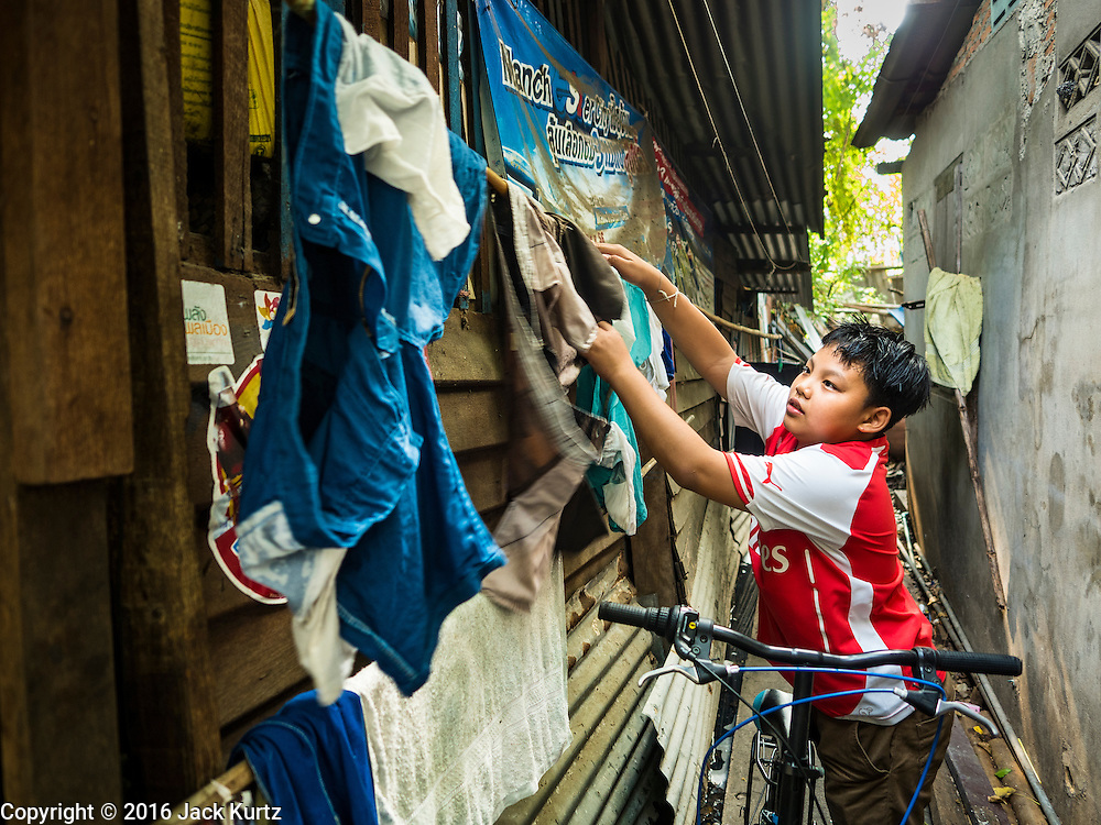 07 APRIL 2016 - BANGKOK, THAILAND: A boy hangs his family laundry to dry next to his home in the squatters' community in Mahakan Fort. Mahakan Fort was built in 1783 during the reign of Siamese King Rama I. It was one of 14 fortresses designed to protect Bangkok from foreign invaders, and only of two remaining, the others have been torn down. A community developed in the fort when people started building houses and moving into it during the reign of King Rama V (1868-1910). The land was expropriated by Bangkok city government in 1992, but the people living in the fort refused to move. In 2004 courts ruled against the residents and said the city could take the land. The final eviction notices were posted last week and the residents given until April 30 to move out. After that their homes, some of which are nearly 200 years old, will be destroyed.       PHOTO BY JACK KURTZ