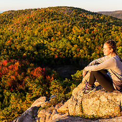 "A young woman enjoys the view from the trail on ""The Beehive"" in fall in Maine's Acadia National Park."
