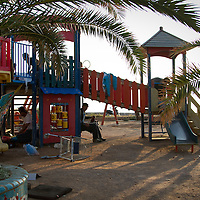 Patras, Greece - men from north Africa use a children's play area as a temporary shelter from bad weather and other dangers of sleeping rough. <br /> The sleeping arrangements for migrants and refugees in Patras has been split into different areas depending on country of origin. Areas of the city have become home to individuals from the Magreb, Sudan, Somalia, Afghanistan, Iraq and the many other nationalities temporarily in the city.