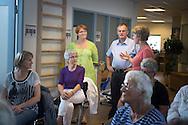 Nørager Fysioterapis Marit Larsen Bech (i rød t-shirt) har besøg af Anni Winther, borgmester, Rebild Kommune og Gert Fisher, borgmesterkandidat samt fysioterapeuternes regionsformand Gitte Nørgaard (i grønt). Her møder de et hold som orienteres om slidgigt. Foto: © Michael Bo Rasmussen / Baghuset. Dato: 04.09.13 Presseudsendelse. Kan frit anvendes ved omtale.
