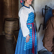 """A costumed woman interprets history and bakes bread in the Barracks building at Fort Ross. Fort Ross State Historic Park preserves a former Russian colony (1812-1842) on the west coast of North America, in what is now Sonoma County, California, USA. Visit Fort Ross and dramatic coastal scenery 11 miles north of Jenner on California Highway One.  Initially, sea otter pelts funded Russian expansion, but by 1820, overhunting motivated the Russian-American Company to introduce moratoriums on hunting seals and otters, the first marine-mammal conservation laws in the Pacific. Russian voyages greatly expanded California's scientific knowledge. For centuries before Europeans arrived, this site was called Metini and had been occupied by the Kashaya band of Pomo people who wove intricate baskets and harvested sea life, plants, acorns, deer, and small mammals. Sponsored by the Russian Empire, """"Settlement Ross"""" was multicultural, built mostly by Alaskan Alutiiq natives and occupied mostly by native Siberians, Alaskans, Hawaiians, Californians, and mixed Europeans. Renamed """"Ross"""" in 1812 in honor of Imperial Russian (Rossiia), Fortress Ross was intended to grow wheat and other crops to feed Russians living in Alaska, but after 30 years was found to be unsustainable. Fort Ross was sold to John Sutter in 1841, and his trusted assistant John Bidwell transported its hardware and animals to Sutter's Fort in the Sacramento Valley. Fort Ross is a landmark in European imperialism, which brought Spanish expanding west across the Atlantic Ocean and Russians spreading east across Siberia and the Pacific Ocean. In the early 1800s, Russians coming from the north met Spanish coming from the south along the Pacific Coast of California, followed by the USA arriving from the east in 1846 for the Mexican-American War. Today, Fort Ross is a California Historical Landmark and a National Historic Landmark. For licensing options, please inquire."""