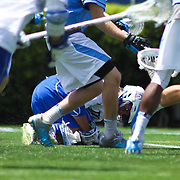 Duke Attacker Josh Dionne (8), CENTER, clutches his right knee after taking a hard check during the second half of a NCAA Division I Men's Lacrosse Tournament game between the Defending national champion Duke and No. 8 ranked Johns Hopkins Sunday, May. 18, 2014 at Delaware Stadium in Newark, DEL
