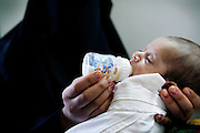 A newborn suffering from a heart and kidney defect, is drinking milk while held by the mother, inside the children's ward of Fallujah General Hospital, Iraq. Around 15 per cent of children at the hospital are now being born with some sort of congenital defect. The average elsewhere in the world is believed to be between 2 and 4 per cent.