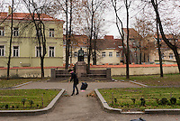 A woman rakes leaves from the grounds of a small park in Vilnius, Lithuania