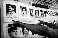 Men point to their missing relatives in street display of faces of Iraqis arrested and disappeared by Saddam Hussein's regime in the 1980's and 1990's.