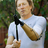 Bob Radocy of TRS Inc. prepares to swing a golf club with a golf hand replacement at his home in Boulder, Colorado August 20, 2009. Radocy designs and builds prosthetic attachments that allow amputee athletes to participate in multiple sports. The golf hand stores energy on the backswing improving power through the downstroke. REUTERS/Rick Wilking (UNITED STATES)
