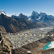 The trekkers' peak of Gokyo Ri (17,575 feet or 5357 meters elevation) gives a wide view of the Khumbu region and Sagarmatha National Park, in the Himalaya Range, Nepal. See four of the world's six highest peaks: Cho Oyu (far left), Mount Everest (center left), adjacent Lhotse, and distant pyramid of Makalu (all over 8,000 meters elevation).  The largest glacier in Nepal, Ngozumpa Glacier, flows along the valley floor covered in gray rocks, and a side moraine dams Gokyo Lakes. Left of green Third Gokyo Lake is Gokyo village (15,583 feet / 4750 meters), a small cluster of teahouses for trekkers and climbers. Sagarmatha National Park was created in 1976 and honored as a UNESCO World Heritage Site in 1979. Panorama stitched from 8 photos.