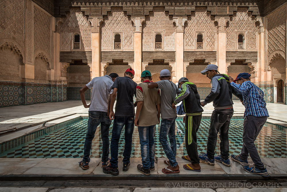 A group of boys play with the reflections of their images in the pool inside the main courtyard of Medersa Ben Youssef in Marrakech, Morocco.