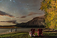 A nightscape scene at Linnet Lake area in Waterton Lakes National Park, looking east over Upper Waterton Lake and toward Vimy Peak, with autumn stars rising in the east, and autumn trees in full colout. The red chairs are the iconic chairs Parks Canada places at many viewpoints in National Parks and Historic Sites. This was a very windy night!<br /> <br /> This is a frane from a time-lapse, at ISO 6400 and f/2.2 with the Nikon D750 and Sigma 24mm lens, for 20 seconds. Passing car headlights provided the foreground light painting.