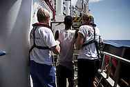 Italy: MSF Dignity1: A sick migrant rescued at sea is helped by MSF doctors on the Dignity1 on August 23, 2015. Alessio Romenzi