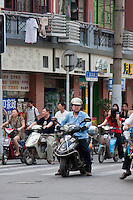 moped riders wait at the lights in Shanghai China