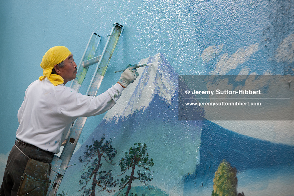 Penki-e (painter who uses paints) Morio Nakajima (wearing yellow head towel), adds shadow detail to his fresh mural of Mount Fuji, over the top of an older similar view by painter Hayakawa Toshimitsu, at the 'Moto No Yu' sento (public bath house) in Shinozaki, in eastern Tokyo, Japan, on Thursday 23rd June 2011.  Nakajima-san and Kiyoto Maruyama are the two remaining painters of Mt Fuji murals in the Kanto area of Japan. Nakajima-san currently undertakes approximately 70 such mural assignments a year, and they each cost the sento owners approximately JPY 100,000.  Mizuki Tanaka,  a graduate of art history, has been an apprentice to Nakajima-san for 6 years but has not yet progressed to the level where she is allowed to paint the Mt Fuji itself, at present she paints the other background details of the mural but not the mountain itself.