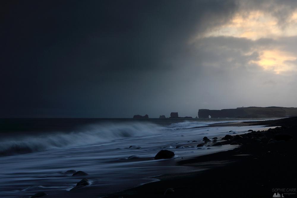 Dusk at Reynisfjara Beach near Vik in Southern Iceland, looking towards Dyrhólaey