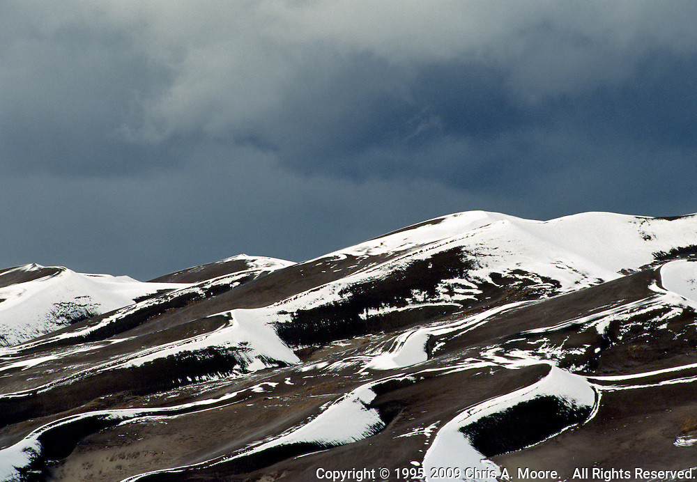 Dark storm clouds build up over the dunes with existing snow at the Great Sand Dunes National Monument, March 1995