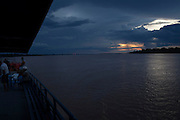 Dramatic skys as another day closes out in the Amazon aboard the Avenger. The Avenger III is a passenger ship making the twice a month journey from the frontier town of Tabatinga in the Tr&ecirc;s Fronteiras region of Northwestern Brazil, to the capital of the State of Amazonas, Manaus. It&rsquo;s also where the Rio Amazonas enters Brazil from its source in neighboring Peru. <br /> <br /> Carrying passengers and crew totaling almost 200 and small cargo, the ship meanders its way along the Rio Amazonas and Rio Solimoes for four days and three nights. Stopping at half a dozen or so makeshift ports en-route, the service provides a vial link for communities along the river to get products to the city and more importantly, in the absence of roads or airfields, provide a means for the sick to reach care in the city of Manaus.<br /> <br /> For those not fortunate to be accommodated in one of the two or three cabins available, home is space found for a self supplied hammock amongst the kaleidoscopic web of coloured fabrics. <br /> <br /> By the second day, negotiating a stroll from port to starboard can seem more like negotiating an assault course of tangled ropes and personal baggage deliberately piled high to protect ones personal space.<br /> <br /> Food served three times daily is adequate, a staple of soups, chicken, rice and noodles. An &lsquo;entertainment&rsquo; deck on the top floor provides ample opportunity to be social engaging in card and board games with beer swilling, chain smoking locals.