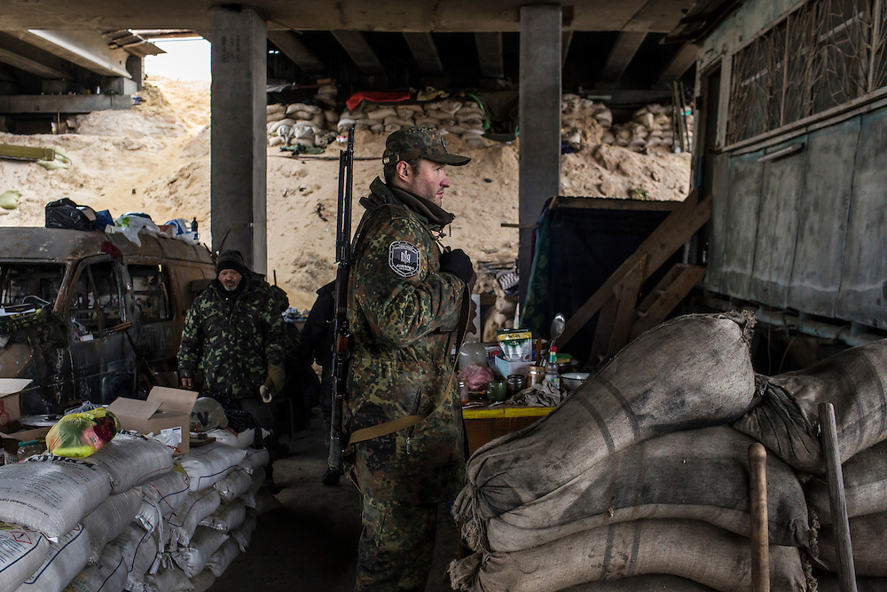 PERVOMAISKE, UKRAINE - NOVEMBER 17, 2014: Skala, center, a member of the 5th platoon of the Dnipro-1 brigade, a pro-Ukraine militia, at their post underneath a bridge in Pervomaiske, Ukraine. CREDIT: Brendan Hoffman for The New York Times