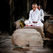2 Buddhist nuns doing their meditation inside the ruins of Angkor Wat.