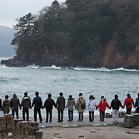 Students from across Japan form a line and hold hands at dawn, as participants in the Project HumanBand which attempted to form an unbroken line of participants along the tsunami-devastated coastline of north east Japan, on the 1 year anniversary of the March 11th 2011 magnitude 9 earthquake and subsequent tsunami, in Minami-Sanriku, Tohoku region,  Japan on Sunday 11th March 2012.