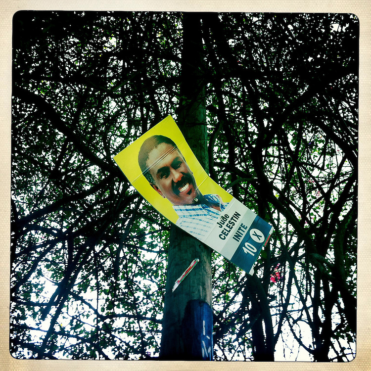 A campaign poster for Jude Celestin hangs in a tree on Wednesday, April 4, 2012 in Port-au-Prince, Haiti.