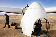 Gansu, China - 26 Feb 2010. Maintenance workers fix the blades of a windmill at Guazhou wind farm near Yumen, Gansu province, China. China has set a target for renewable energy consumption of 40 percent of the market by the year 2050.Photographer: Markel Rendondo/Greenpeace.