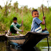 Boys steer their way around the backwaters off Inle Lake, Myanmar.