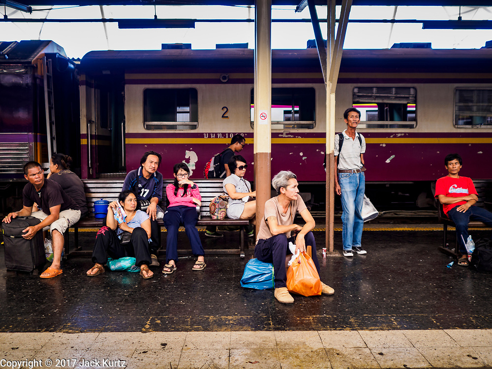 """11 APRIL 2017 - BANGKOK, THAILAND:  Holiday travelers wait for their train during the Songkran travel period at Hua Lamphong train station in Bangkok. Songkran is the traditional Thai Lunar New Year. It is celebrated, under different names, in Thailand, Myanmar, Laos, Cambodia and some parts of Vietnam and China. In most places the holiday is marked by water throwing and water fights and it is sometimes called the """"water festival."""" This year's Songkran celebration in Thailand will be more subdued than usual because Thais are still mourning the October 2016 death of their revered Late King, Bhumibol Adulyadej. Songkran is officially a three day holiday, April 13-15, but is frequently celebrated for a full week. Thais start traveling back to their home provinces over the weekend; busses and trains going out of town have been packed.    PHOTO BY JACK KURTZ"""