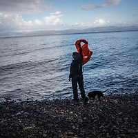 A volounteer signaling the landing area to an incoming boat, north Lesbos shore. FEDERICO SCOPPA/CAPTA