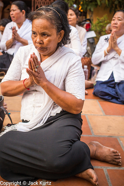 "03 FEBRUARY 2013 - PHNOM PENH, CAMBODIA: A woman prays on the street during the final Buddhist chanting service for former Cambodian King Norodom Sihanouk in the crematorium built for the King's funeral at the National Museum in Phnom Penh. Norodom Sihanouk (31 October 1922 - 15 October 2012) was the King of Cambodia from 1941 to 1955 and again from 1993 to 2004. He was the effective ruler of Cambodia from 1953 to 1970. After his second abdication in 2004, he was given the honorific of ""The King-Father of Cambodia."" He served as puppet head of state for the Khmer Rouge government in 1975-1976, before going into exile. Sihanouk's actual period of effective rule over Cambodia was from 9 November 1953, when Cambodia gained its independence from France, until 18 March 1970, when General Lon Nol and the National Assembly deposed him. Upon his final abdication in 2004, the Cambodian throne council appointed Norodom Sihamoni, one of Sihanouk's sons, as the new king. Sihanouk died in Beijing, China, where he was receiving medical care, on Oct. 15, 2012. His cremation will take place on Feb. 4, 2013. Over a million people are expected to attend the service.     PHOTO BY JACK KURTZ"