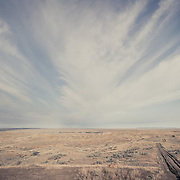 wild prairie of eastern montana, road leading into prairie with wispy clouds sky conservation photography - montana wild prairie