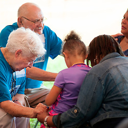25 JULY 2015 -- FERGUSON, Mo. -- Blessed Teresa of Calcutta parishioners Ceil Vossmeyer (left) and her husband Ralph Vossmeyer pray with participants during Convoy of Hope, a faith-based outreach program at Forestwood Park in Ferguson, Mo. Saturday, July 25, 2015. The event included health check ups, haircuts, career counseling, play areas for children, food for needy families and spiritual counseling.<br /> <br /> Photo by Sid Hastings.