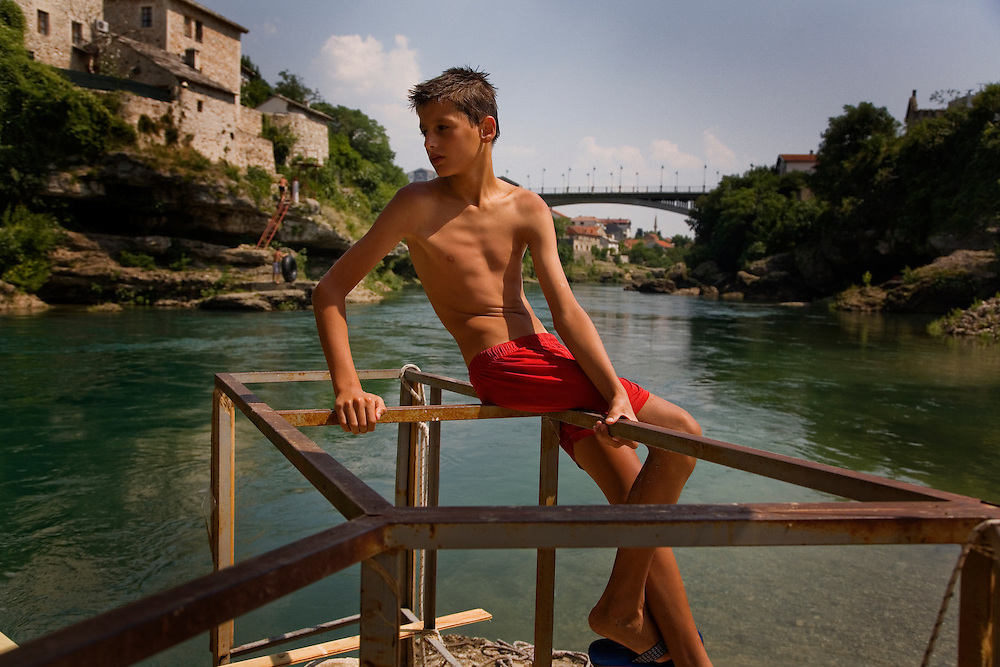 """Boys from Mostar along the banks of the Neretva...Divers and tourists at Mostar's famous Old Bridge (Stari Most) in Bosnia and Herzegovina. This bridge is the city and region's biggest tourist attraction and there are busses full of tourists coming in from Sarajevo and Dubrovnik, Croatia. For 25euros tourists can train to jump from the bridge themselves, under supervision from the """"professional"""" Mostar divers known as the Mostari. .."""