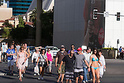 Een vrouw in bikini loopt met een groep mannen over de strip in Las Vegas.<br />